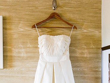 Ashleys short wedding dress hangs in her bridal suite before her Ann Arbor botanical garden wedding