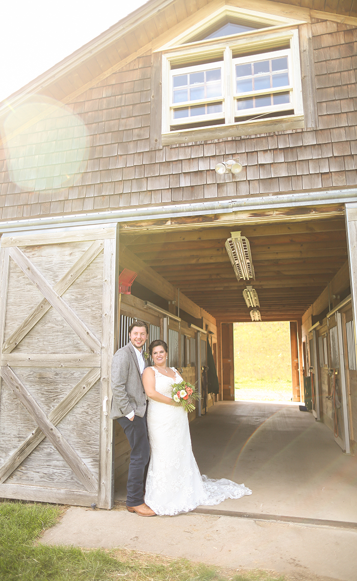 Allison & Nick stand in front of the beautiful working horse barn at the Garvey Family Wedding Barn in Traverse City, Michigan