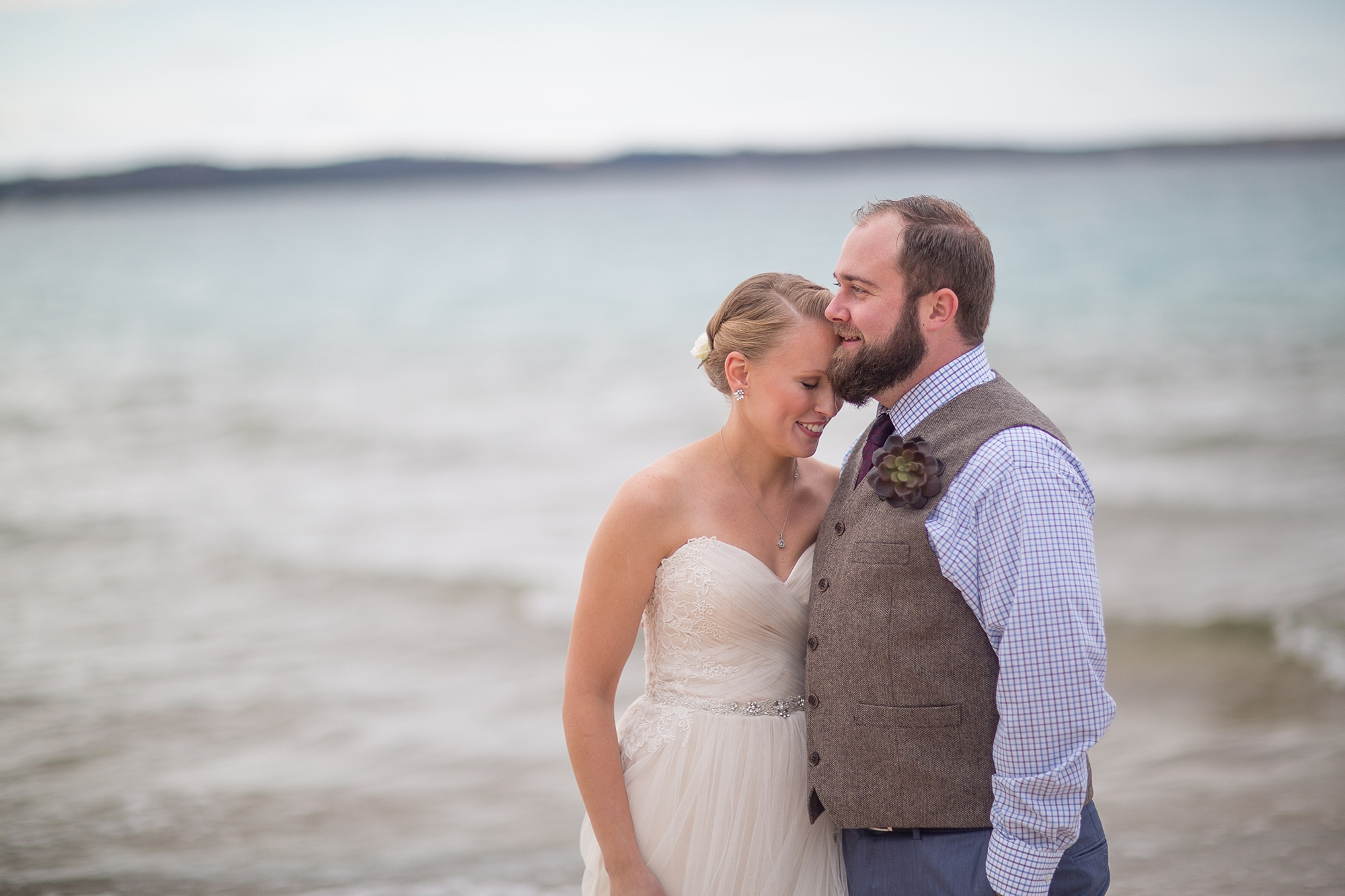 Couple Cuddles on the shores of Lake Michigan at the Homestead Resort