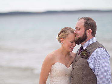 Heather & Josh cuddle on the beach of Lake Michigan at the Homestead Resort in Glen Arbor.