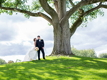 Katie & Ryan share a moment under a huge oak tree during their Bloomfield Hills wedding