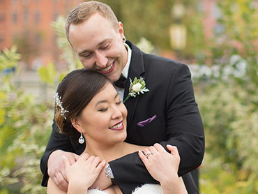 Gabby and Aaron hug in the gardens of downtown Kalamazoo, Michigan on their wedding day.