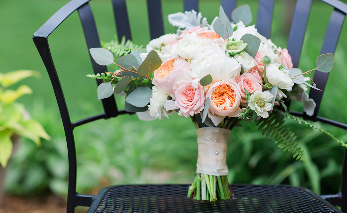 Maureen's bridal bouquet, by A Moment in Time, rest on a chair outdoors before their wedding ceremony in Farmington Hills, Michigan.