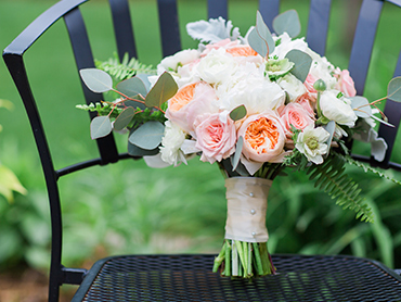Maureens bridal bouquet, by A Moment in Time, rest on a chair outdoors before their wedding ceremony in Farmington Hills, Michigan.