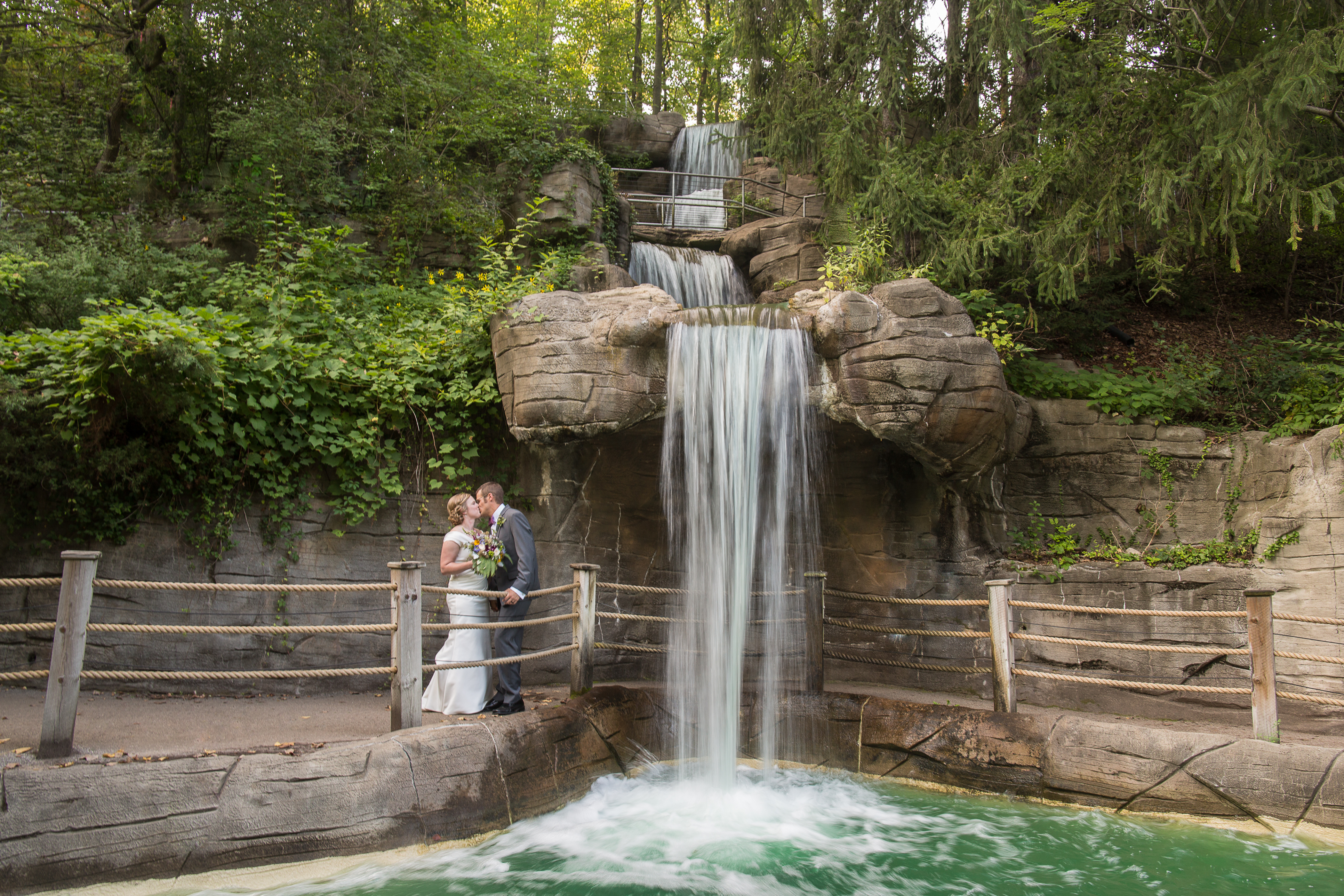 Elise & Chris stand under a waterfall on their wedding day