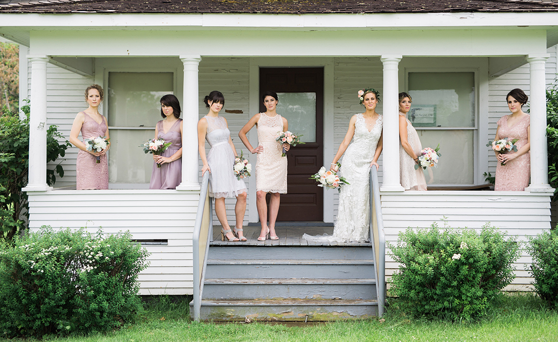 Maureen and her beautiful bridesmaids stand outside of a historical building on the grounds of the Greenmead Historical Village in Farmington Hills, Michigan.