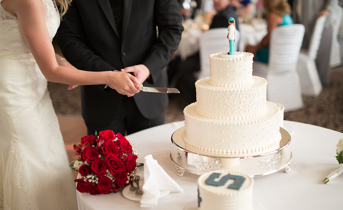 Cutting their beautiful personalized wedding cakes at their wedding reception in Plymouth, Michigan
